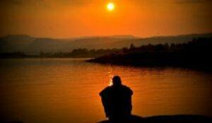 Silhouette of person looking at water