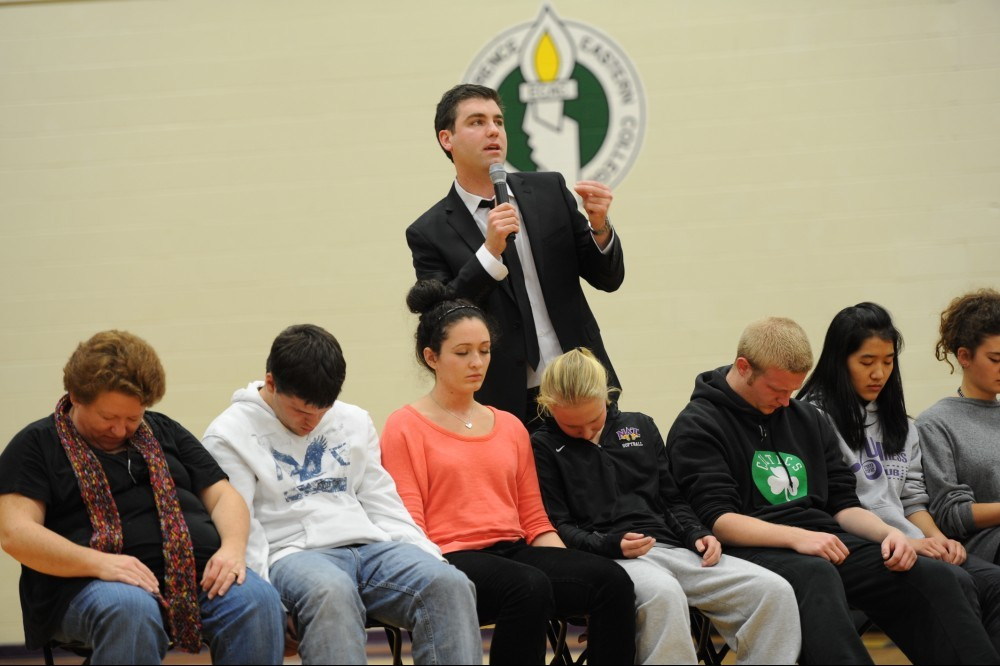 Picture of stage hypnotist performing hypnosis on volunteers.