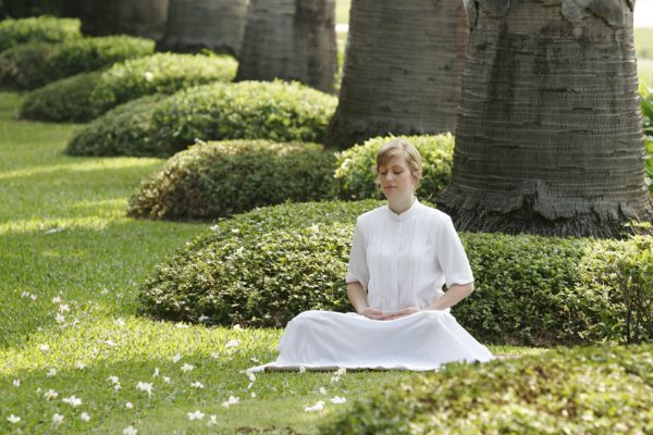 Lady sitting on grass meditating