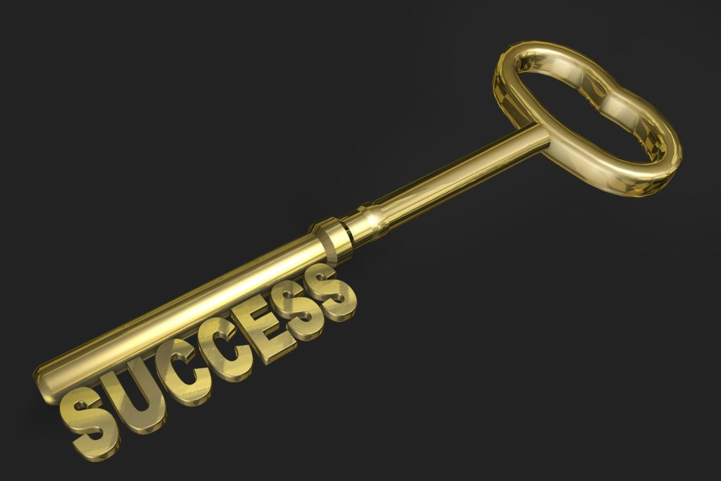 A gold key with the word success forming the bottom part of the key