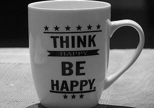 """White cup with words """"Think Happy, Be Happy"""""""