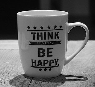 "White cup with words ""Think Happy, Be Happy"""