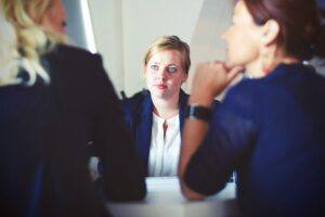Anxious woman listening to woman talking in a group