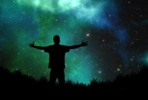 Person with arms outstretched towards the universe